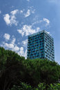 Skyscraper a with modern style emerges from a group of trees Stock Photo