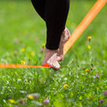 Slack line in the city park lady practising slacklining is a practice balance that typically uses nylon or polyester webbing Royalty Free Stock Photo