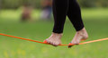 Slack line in the city park lady practising slacklining is a practice balance that typically uses nylon or polyester webbing Stock Photo