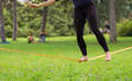 Slack line in the city park lady practising slacklining is a practice balance that typically uses nylon or polyester webbing Stock Images