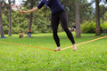 Slack line in the city park lady practising slacklining is a practice balance that typically uses nylon or polyester webbing Stock Image
