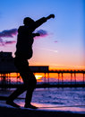 Slack liner a man practises his lining on the beach at sunset in front of the victorian pier in aberystwyth ceredigion west wales Stock Photo