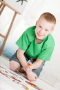 Slanted view of boy kneeling on painting in green shirt and blue jean shorts near easel light background Stock Photos