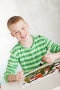 Slanted view of smiling boy with paint brush wearing green striped long sleeve shirt in hand against a light background Stock Photography