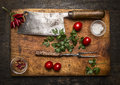Slasher meat fork meat pepper salt tomatoes, fresh herbs on wooden cutting board top view on rustic wooden background Royalty Free Stock Photo