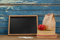 Slate, chalk, apple, lunch bag and books Royalty Free Stock Photo