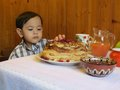 Slavic holiday pancake in house baby boy sitting at a table with a plate of pancakes jam cup and jug Stock Photography