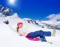 Sled sliding from the mountain slope happy girl on with her hands lifted wearing ski mask in mountains Stock Images
