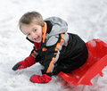 Sledding on snow happy young boy out playing in the his sledge Stock Photography