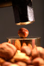 Sledgehammer to crack a nut expression using with nuts in foreground Royalty Free Stock Photos