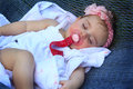 Sleeping baby a cute girl laying in a hammock with a pacifier wearing a pink headband and white dress Royalty Free Stock Image