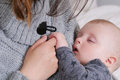 Sleeping baby gently holding mother`s finger Royalty Free Stock Photo