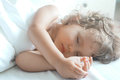 Sleeping beauty baby girl in white bed Royalty Free Stock Photo