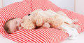 Sleeping cute little baby on red and white stripes pillow Stock Image
