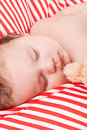 Sleeping cute little baby on red and white stripes pillow Stock Photos