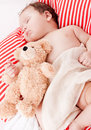 Sleeping cute little baby on red and white stripes pillow Stock Photography