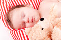 Sleeping cute little baby on red and white stripes pillow Royalty Free Stock Image