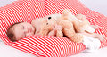 Sleeping cute little baby on red and white stripes pillow Royalty Free Stock Images