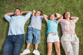 Sleeping family lying on the grass in a row park sunny day Stock Image