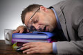 Sleeping on the job exhausted businessman falling asleep at his office desk Royalty Free Stock Photo