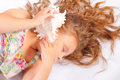 Sleeping little girl with seashell in her hands Royalty Free Stock Photos