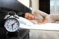 Sleeping man with alarm clock in foreground Stock Photo