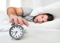 Sleeping man disturbed by alarm clock early mornin lazy ringing morning Stock Photo