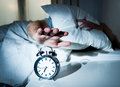 Sleeping man disturbed by alarm clock early mornin tired with pillow on his head switching off morning Stock Images
