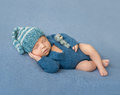 Sleeping newborn baby in blue jumpsuit and hat Royalty Free Stock Photo