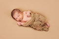 Sleeping newborn baby boy a week old wrapped in gauzy beige fabric and on a beige fleece blanket Stock Photos