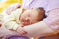 Sleeping newborn baby on mother hands Stock Photos