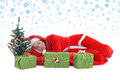 Sleeping santa in red under tree Stock Photography