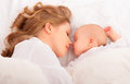 Sleeping together. mother embraces the newborn baby in bed Royalty Free Stock Photo