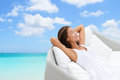 Sleeping woman relaxing lounging on a outdoor sofa white day bed lounger beach ocean background asian girl lying down laid back Royalty Free Stock Image
