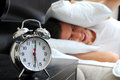 Sleeping young male adult stressed by his alarm clock with his head under the pillow in the bedroom Stock Photos