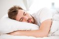 Sleeping young man handsome with a beard in white bed Royalty Free Stock Photography