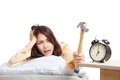 Sleepy Asian girl wake up hit alarm clock with hammer Royalty Free Stock Photo