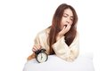 Sleepy Asian girl  wake up  with pillow and alarm clock Royalty Free Stock Photo