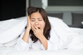 Sleepy Asian woman yawning in bed Royalty Free Stock Photo
