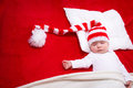 Sleepy baby on red blanket in knitted hat Stock Image