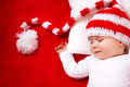 Sleepy baby on red blanket in knitted hat Royalty Free Stock Photos
