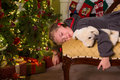 Sleepy with christmas little girl on a sofa near the tree Stock Photo