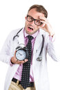 Sleepy exhausted male doctor wearing glasses holding an alarm clock tired after a busy da close up portrait of day on call night Stock Image