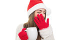 Sleepy girl yawning holding a cup of hot beverage young cute caucasian with eyes closed wearing santa claus beanie hat and gloves Royalty Free Stock Photo