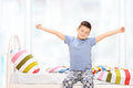 Sleepy little boy in pajamas stretching himself seated on a bed at home Stock Images