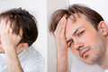 Sleepy man suffers from hangover in the morning near mirror Royalty Free Stock Images