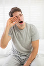 Sleepy man yawning as he rubs his eye in bed young at home Stock Image