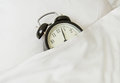 Sleepy morning alarm clock sleeping in white linen bed Royalty Free Stock Photos