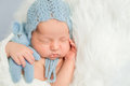 Sleepy newborn boy in blue hat knitted with toy on white fluffy blanket Stock Images
