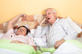 Sleepy senior couple yawning in bed men and women Stock Images